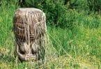 Imagem de um ser similar a uma mulher esculpida em pedra com cabelos que se misturam com as plantas do chão.