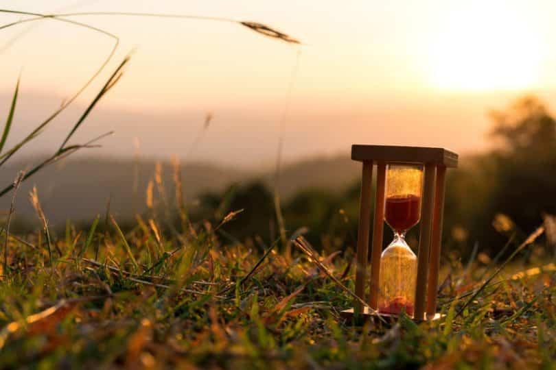 Ampulheta em grama com sol refletindo