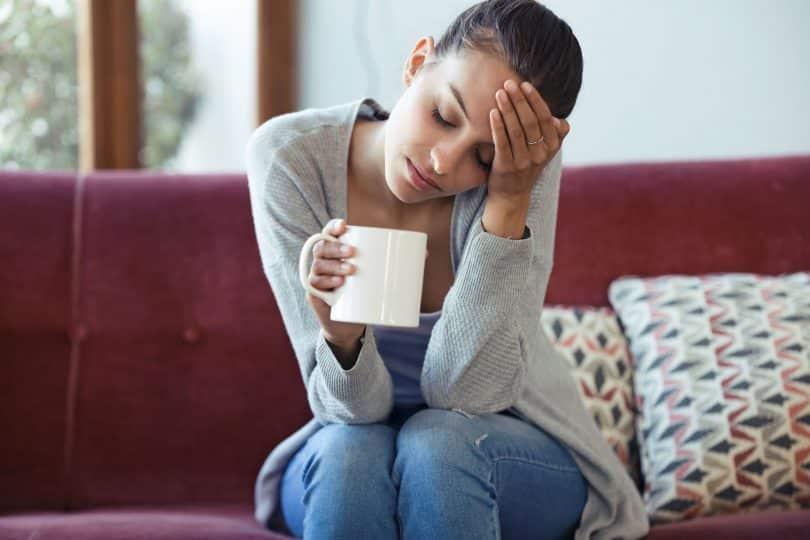Mulher branca de olhos fechados sentada num sofá vermelho segurando uma caneca branca com uma mão e a outra levada à testa.