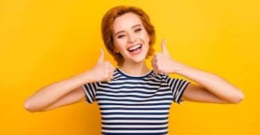 Mulher sorrindo fazendo joia com as mãos em fundo amarelo
