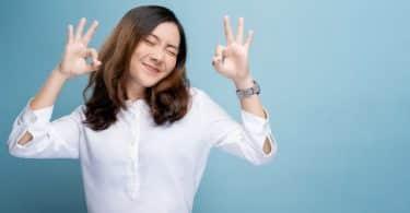 """Mulher sorrindo enquanto faz um sinal de """"OK"""" com ambas as mãos"""