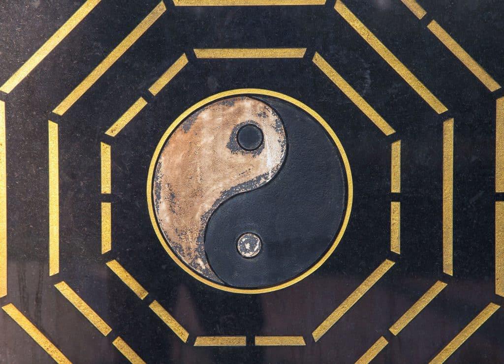 Símbolo do Yin Yang em um mármore com detalhes em dourado ao redor