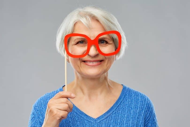 Imagem de uma senhora de cabelos brancos feliz segurando um óculos gigante de armação vermelha.
