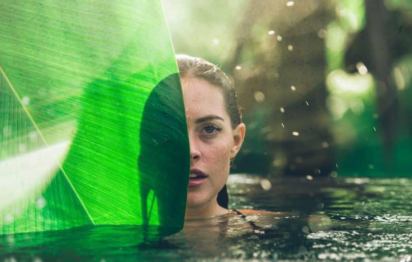 Mulher nadando em um lago, com uma grande folha cobrindo metade de seu rosto