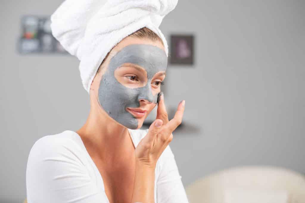 Mulher aplicando argila cinza no rosto