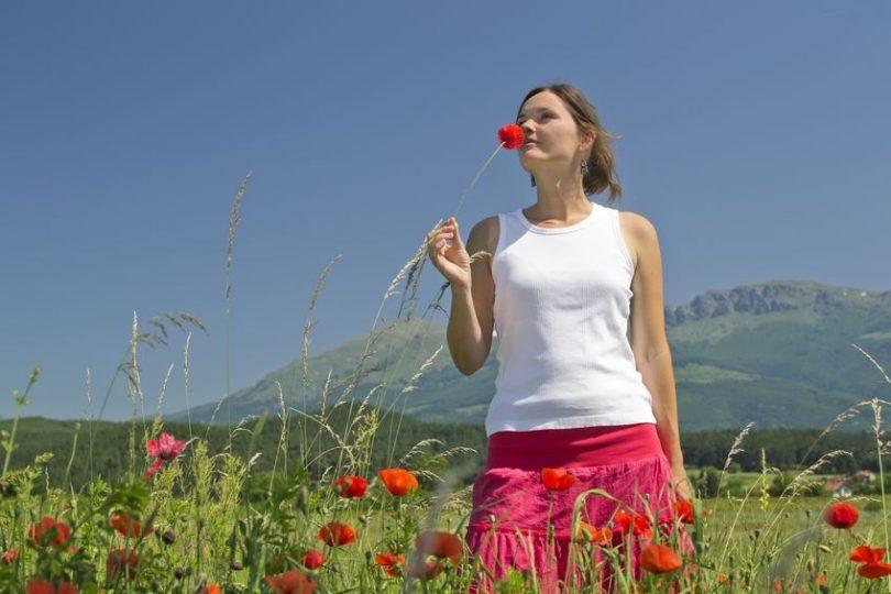 Mulher em capo de flores com uma na mão cheirando