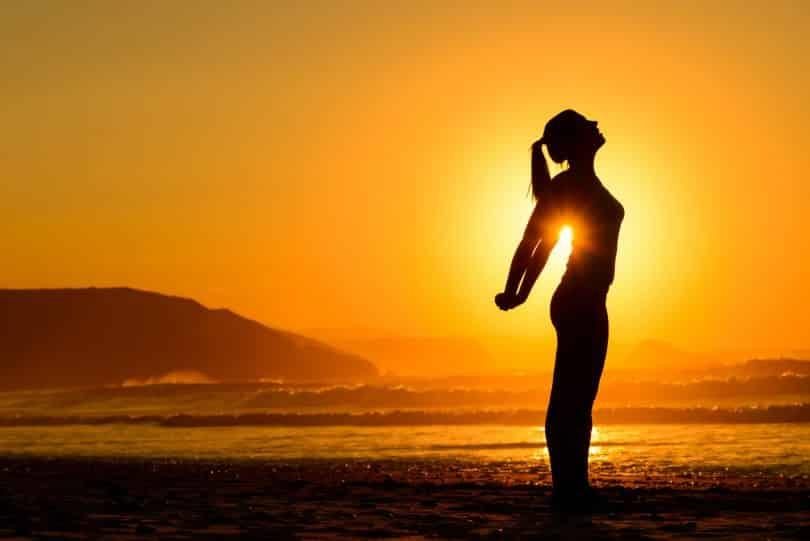Mulher em pé se alongando na praia durante o pôr-do-sol