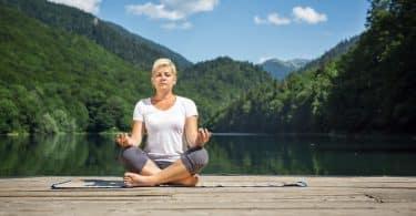 Mulher sentada meditando em ponte com lago ao fundo