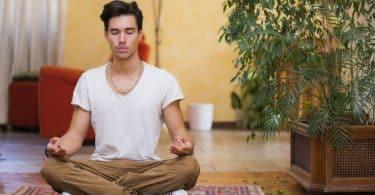 Homem sentado em tapete com olhos fechados meditando