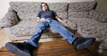 Homem jogado no sofá com controle no colo