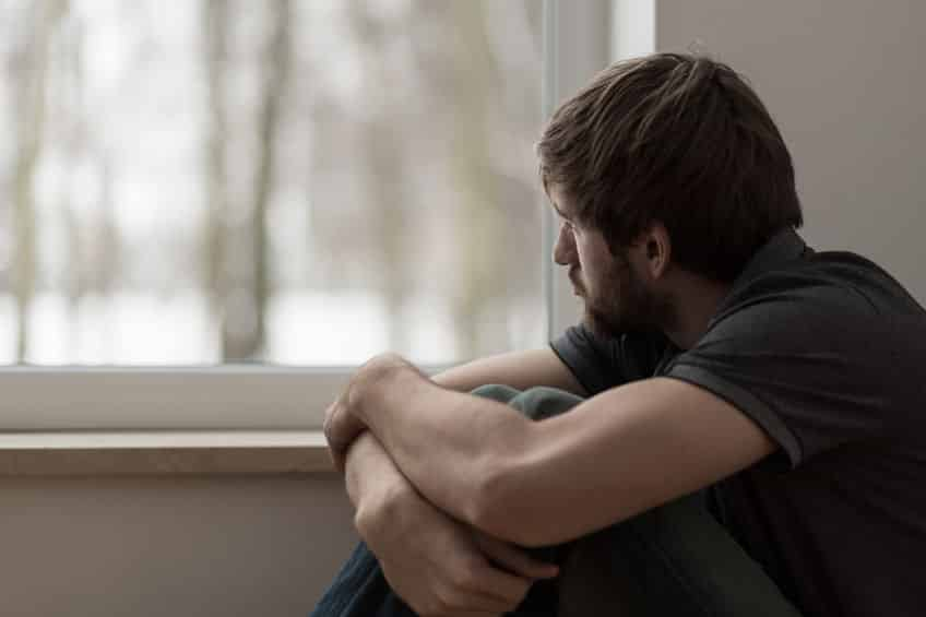 Homem olhando pela janela, sentado, com expressão triste.