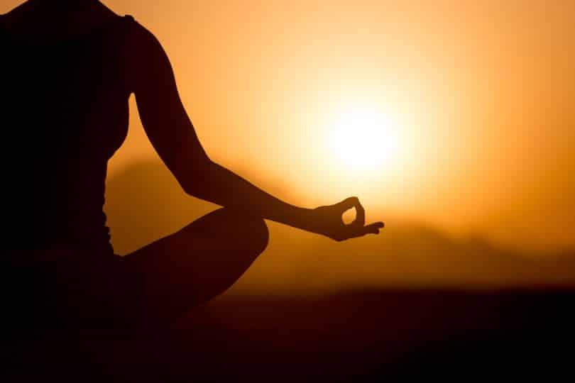 Mulher meditando e nascer do sol ao fundo