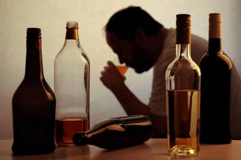 Homem bebendo ao lado de garrafas de bebida alcoólica.