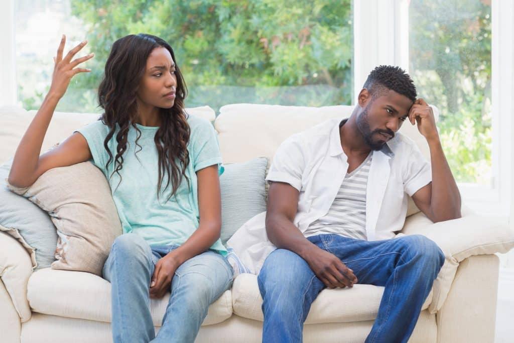 Homem e mulher negros sentados num sofá branco com expressões impacientes