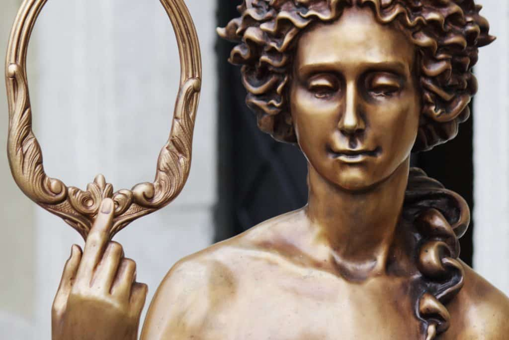 Imagem em bronze da estátua daa deusa Afrodite segurando um espelho.
