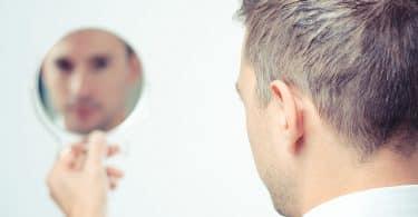 Homem branco segurando um espelho olhando à si mesmo.
