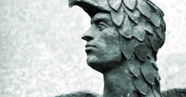 Cabeça da estátua de Ícaro, coberta por uma espécie de escamas com o rosto à mostra. É visível uma pequena parte de suas asas.