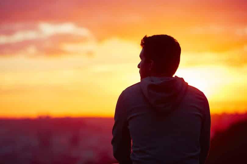 Homem sentado olhando o pôr do sol.