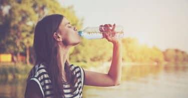 Mulher branca bebendo água da garrafa numa praça