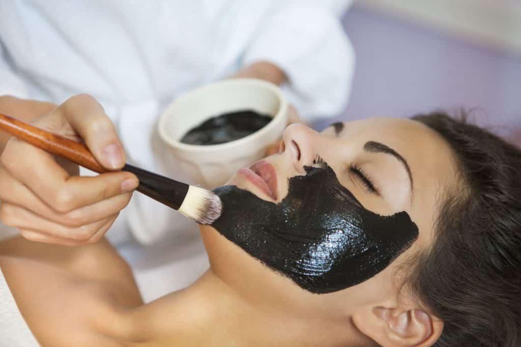 Mulher aplicando com um pincel argila preta no rosto de outra mulher