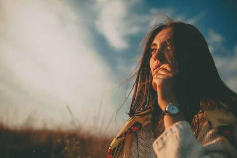 Mulher branca com cabelos lisos num campo e mão levada à boca