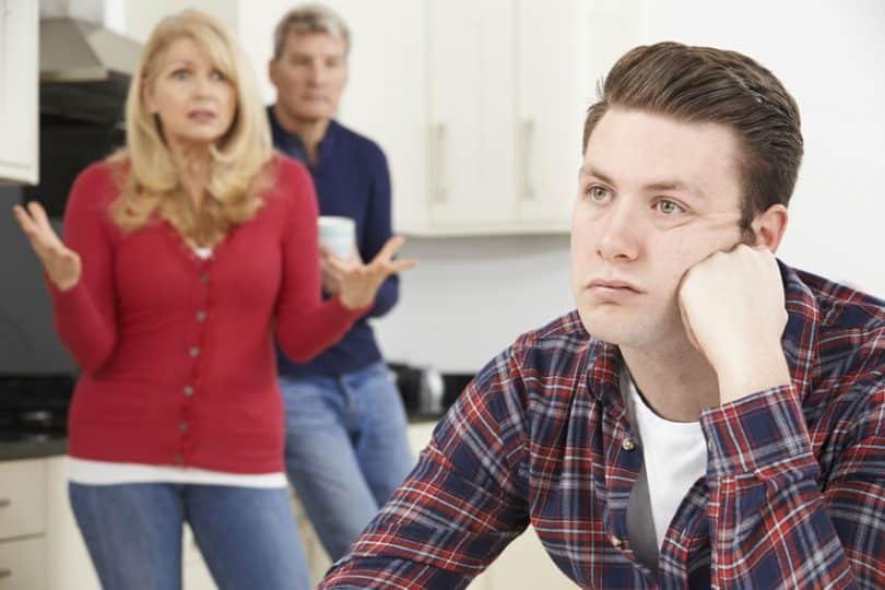 Filho adulto sentado ao lado de seus pais, que reclamam, em pé.