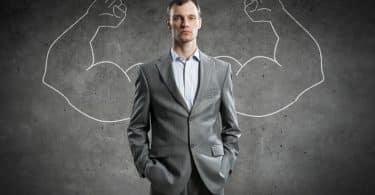 Homem com roupas sociais e expressão séria com braços musculosos desenhados atrás de sua figura.