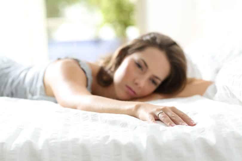 Mulher deitada na cama, com expressão triste.