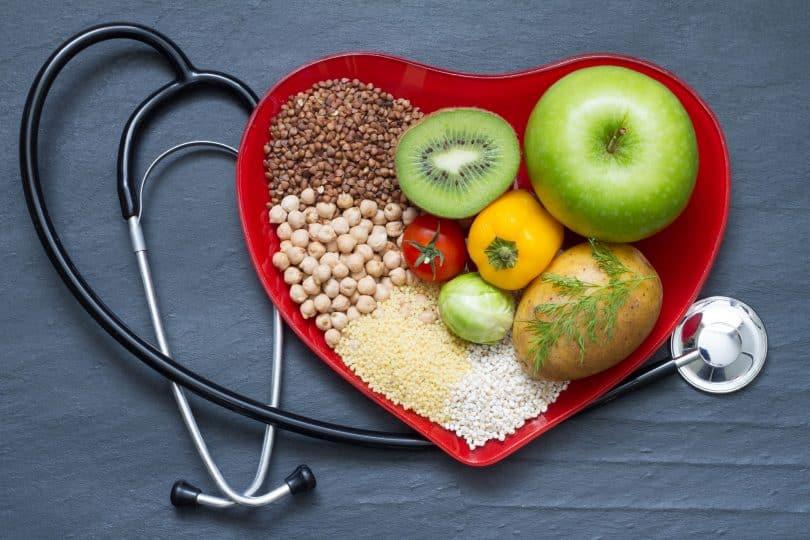 Pote em formato de coração com frutas e cereais, ao lado de um estetoscópio.