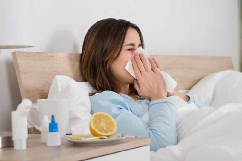 Mulher branca deitada numa cama assoando o nariz com um lenço de papel