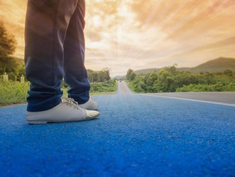 Pessoa caminhando por uma estrada ao pôr do sol.