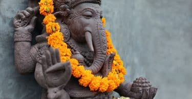 Estátua de Lord Ganesha com um colar de flores laranjas em seu pescoço. Ganesha é um deus com corpo de homem, com quatro braços e a cabeça de elefante.