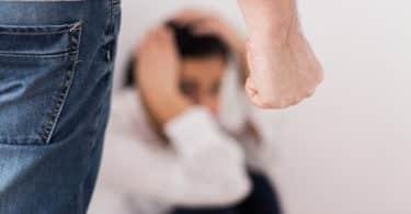 Imagem de uma mulher com medo, sentada no chão e com as mãos cobrindo o rosto. Em sua frente, aparece um homem com a mão fechada insinuando uma agressão física.