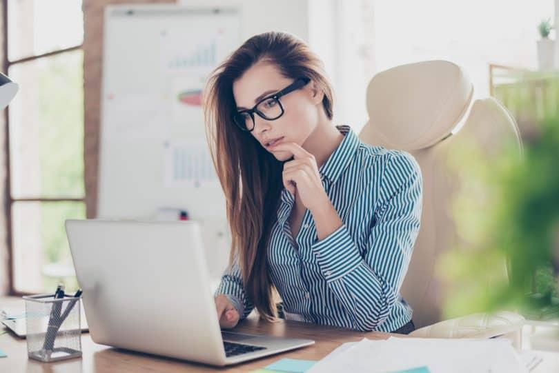 Mulher branca com roupas sociais e mão levada ao queixo olhando um notebook.