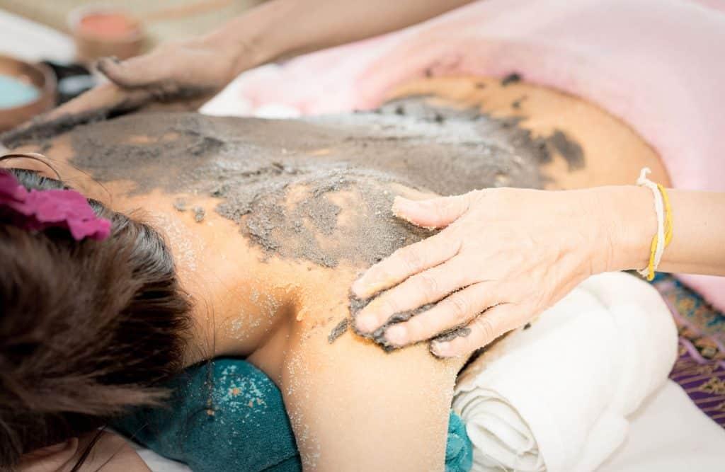 Mulher passando argila nas costas de outra mulher que esta em uma maca