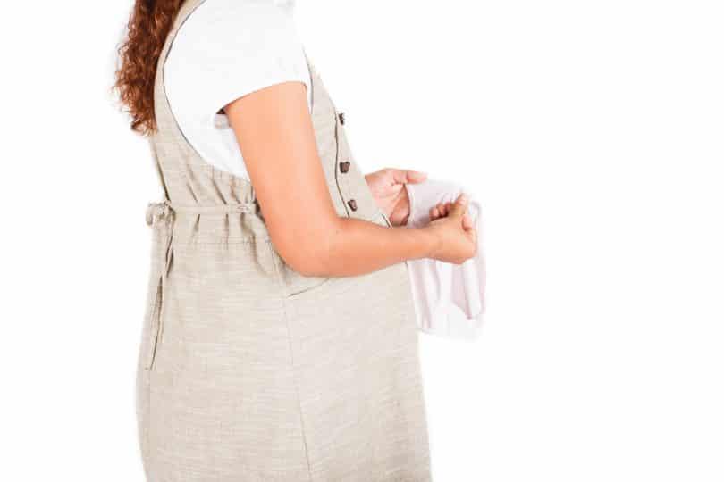 mulher grávida de lado olhando para uma calcinha branca que está em suas mãos.
