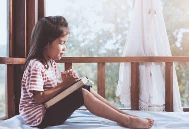 Menina pequena rezando em sua cama com janela ao fundo