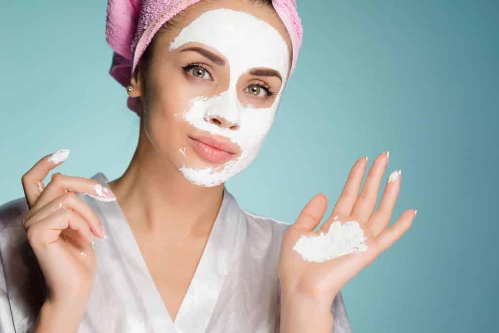 Mulher passando em seu rosto argila branca