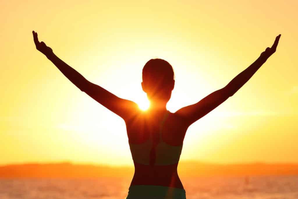 Mulher virada para o horizonte com os braços abertos