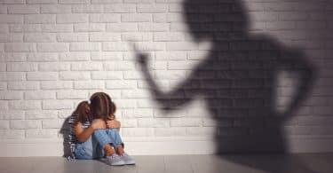 Criança sentada no chão abraçando seus joelhos e ao aldo a sombra de sua mãe