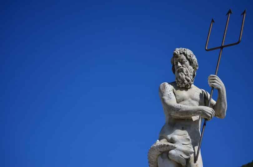 Imagem da estátua de poseidon como um homem barbudo e forte segurando um tridente.