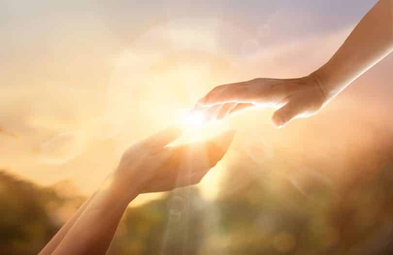 Par de mãos brancas prestes a se tocar com luz do Sol ao fundo