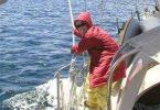 Autora usando um casaco grande vermelho e óculos de sol enquanto veleja.
