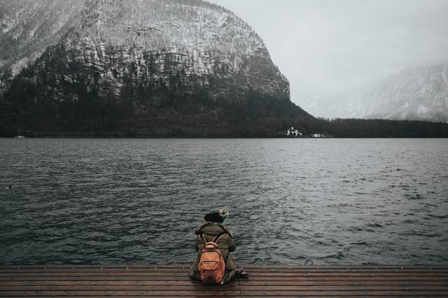 Mulher sentada em deck de madeira com mochila nas costas e rio e montanha ao fundo