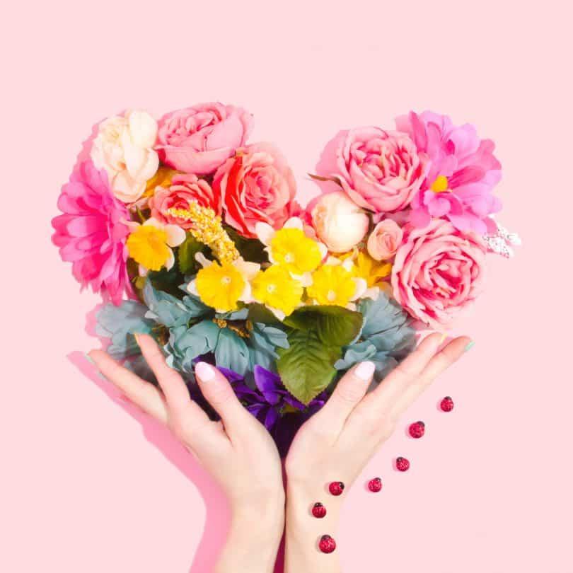 Pessoa contornando com suas mãos um coração feito de flores