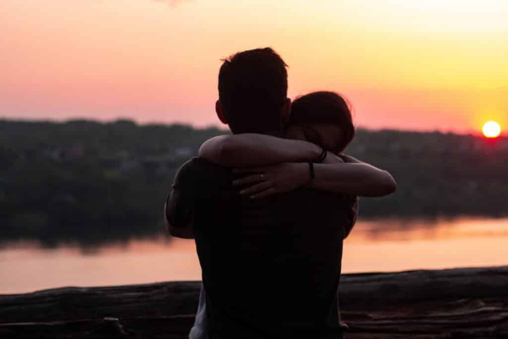 Homem e mulher se abraçando ao lado de um lago