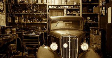 Imagem de um carro antigo estacionado dentro de uma garagem. Ele representa o que é sonhar com carro.