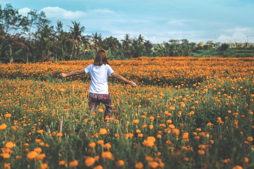 Mulher caminhando em um campo de flores