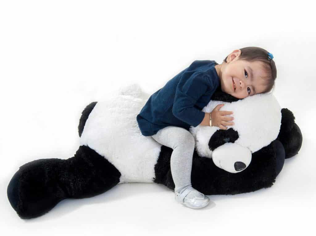 Imagem de uma linda menininha sentada sobre o seu grande urso panda feito de pelúcia.