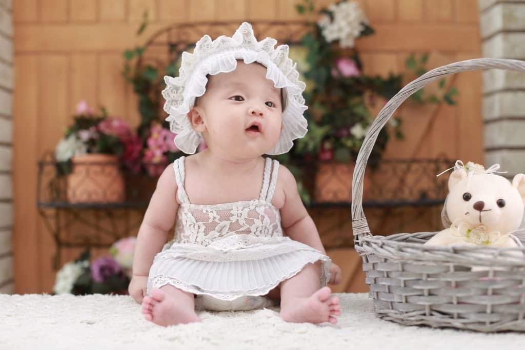 Imagem de uma linda bebê usando um vestidinho e uma touca de renda na cor branca. Ela está sentada sobre um tapete branco e ao lado dela uma cesta de vime com um ursinho dentro.